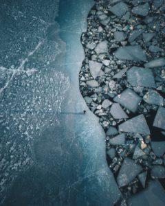 Ein einsamer Mensch auf einer Abbruchkante in der Ostsee an der Küste von Turku, Finnland. Die Eisschollen entstehen durch das passieren von Fähren und Schiffen