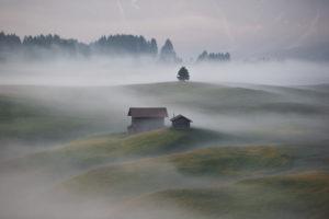 Sonnenaufgang über der Seiser Alm / Alpe di Siusi in den Dolomiten, Südtirol, Italien. Nebel verschleiert die einzelnen Waldabschnitte und Almhütten