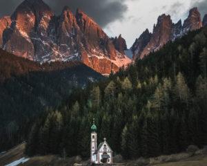 Die Kirche Santa Maddalena im Val di Funes (Vilnößtal) mit der Geisler-Gruppe im Hintergrund im Sonnenuntergang