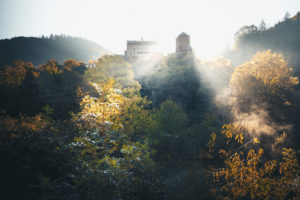 Autumn sunrise over an old castle with sunbeams in the Hunsrück