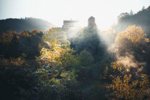 Herbstlicher Sonnenaufgang über einer alten Burg mit Sonnenstrahlen im Hunsrück