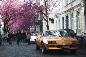 Goldener Oldtimer in der Heerstraße in Bonn am Straßenrand geparkt, während Zuschauer die Kirschblüte bestaunen