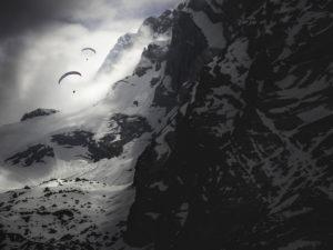 Gleitschirmflieger am Watzmann bei Berchtesgaden in den Wolken und mit Schnee. Dramatische Stimmung
