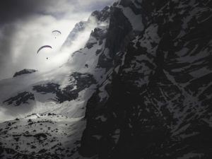 Paraglider pilots on the Watzmann near Berchtesgaden in the clouds and with snow. Dramatic mood