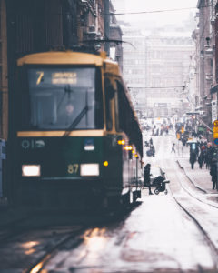 A tram in Helsinki, Finland. In the background a mother with a pram