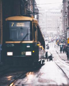 Eine Tram in Helsinki, Finnland. Im Hintergrund eine Mutter mit Kinderwagen
