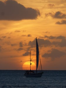 Sail boat in the distance at sea with setting sun