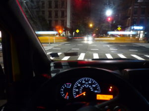 NYC, view of Upper Westside intersection with passing yellow cabs viewed threw the windshield