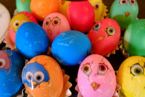 Colored Easter eggs with stickers looking like freshly hatched chickens