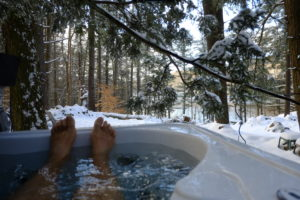Man's feet sticking out of outdoor hot tub during winter