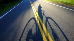 Cyclist's shadow projected or road, Lake Hill, NY
