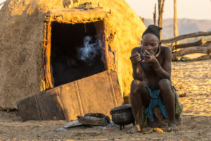 Himba man in front of the mud hut