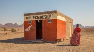 Frau in Traditoneller Kleidung der Holländer vor einem Lebensmittelgeschäft in der Wüste,