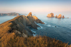 Aussicht über zerklüftete Küste bei Santander / Liencres in ersten warmen, weichen Morgenlicht, Kantabrien, Spanien