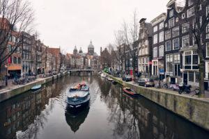 Szene aus Amsterdam mit Gracht, Boot und typischen Häusern