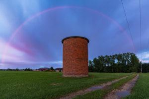 Regenbogen während eines Sonnenuntergangs mit spektakulär gefärbtem Himmel. Im Vordergrund ein Backsteinsilo.