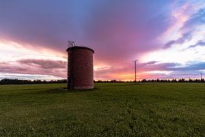 Sonnenuntergang bei Regen. Im Vordergrund ein Backsteinsilo, im Hintergrund ein spektakulär gefärbter Himmel