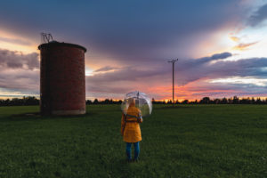 Sunset with rain. In the foreground a person with a raincoat and umbrella and a brick silo, in the background a spectacularly colored sky