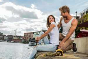 A woman and a man are sitting on the bank of a canal