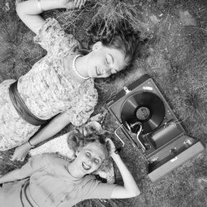 Zwei junge Frauen liegen im Gras und hören die neuesten Schlager vom Electrola Koffergrammophon, Deutschland 1930er Jahre. Two young women lying in a lawn and listening to the lastest hits from their Electrola gramophone, Germany 1930s.