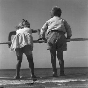 Zwei kleine Kinder turnen an einem Gelände am Strand der Ostsee in Ostpreußen, Deutschland 1930er Jahre. Two little children playing at a railing on the coast of the Baltic Sea at East Prussia, Germany 1930s.