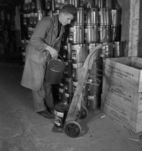 Apprentice at the warehouse with products of food company Mondamin, Germany 1940s.