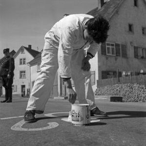 A painter marking parking areas on the street, Germany 1950s.