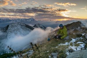 Deutschland, Bayern, Bayerische Alpen, Garmisch-Partenkirchen, Oberer Rißkopf, Wanderer kocht Kaffee auf Berg mit Blick auf die Zugspitze während des Sonnenuntergangs