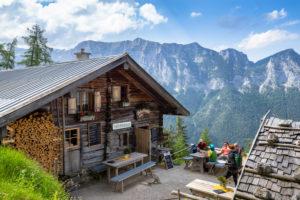 Deutschland, Bayern, Berchtesgadener Land, Ramsau, Gäste auf der Terrasse der Schärtenalm im Hochkaltermassiv mit Blick auf die Reiteralpe