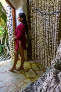 Amerika, Karibik, Große Antillen, Dominikanische Republik, Cabarete, Frau steht in der Türe ihres Bungalows im Natura Cabana Boutique Hotel & Spa und schaut nach draußen