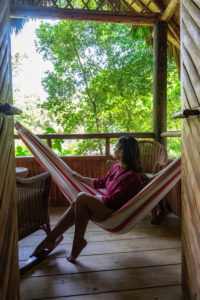 America, Caribbean, Greater Antilles, Dominican Republic, Cabarete, woman sitting in a hammock on the balcony of her bungalow in the Natura Cabana Boutique Hotel & Spa
