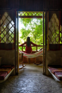 Amerika, Karibik, Große Antillen, Dominikanische Republik, Cabarete, Frau steht auf dem Balkon ihres Bungalows und schaut in den Garten des Natura Cabana Boutique Hotel & Spa