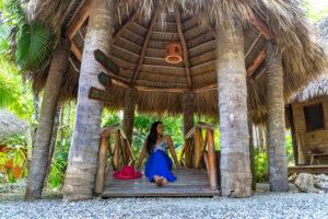 Amerika, Karibik, Große Antillen, Dominikanische Republik, Cabarete, Frau sitzt auf einer kleinen Holzbrücke im Natura Cabana Boutique Hotel & Spa