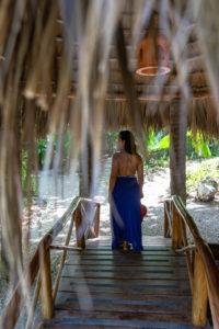 Amerika, Karibik, Große Antillen, Dominikanische Republik, Cabarete, Frau steht auf einer kleinen Holzbrücke im Natura Cabana Boutique Hotel & Spa