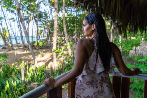 America, Caribbean, Greater Antilles, Dominican Republic, Cabarete, woman looks out from a balcony onto the beach at the Natura Cabana Boutique Hotel & Spa