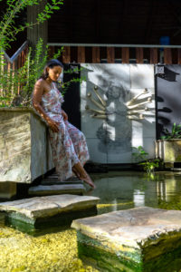 America, Caribbean, Greater Antilles, Dominican Republic, Cabarete, woman enjoys the peace in a fish pond in the yoga area of the Natura Cabana Boutique Hotel & Spa