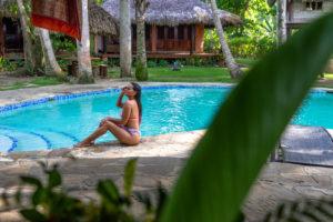 Amerika, Karibik, Große Antillen, Dominikanische Republik, Cabarete, Frau sitzt am Beckenrand des Pools im Natura Cabana Boutique Hotel & Spa