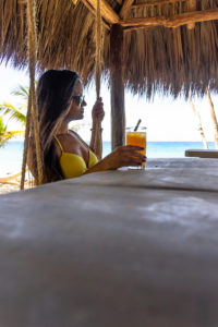 America, Caribbean, Greater Antilles, Dominican Republic, Cabarete, woman sitting on a swing at the beach bar and drinking a cocktail at the Natura Cabana Boutique Hotel & Spa