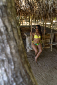 America, Caribbean, Greater Antilles, Dominican Republic, Cabarete, woman sitting on a swing at the beach bar of the Natura Cabana Boutique Hotel & Spa