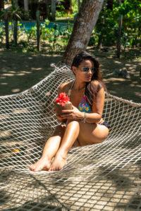 Amerika, Karibik, Große Antillen, Dominikanische Republik, Cabarete, Frau sitzt in einer Hängematte im Natura Cabana Boutique Hotel & Spa und hält eine Kokusnuss in der Hand