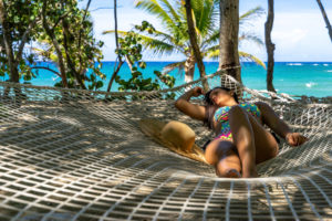 Amerika, Karibik, Große Antillen, Dominikanische Republik, Cabarete, Frau entspannt in einer Hängematte im Natura Cabana Boutique Hotel & Spa