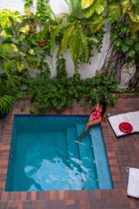 America, Caribbean, Greater Antilles, Dominican Republic, Santo Domingo, Zona Colonial, Hotel Colonial 154 H Boutique, woman sitting by the pool