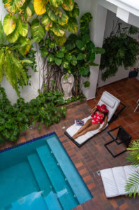 America, Caribbean, Greater Antilles, Dominican Republic, Santo Domingo, Zona Colonial, Hotel Colonial 154 H Boutique, woman with sun hat on a sun lounger by the pool