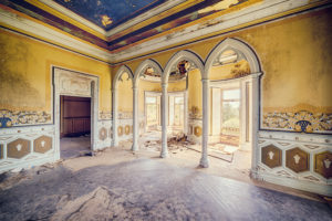 Ballroom in an abandoned castle with columns and blue ceiling