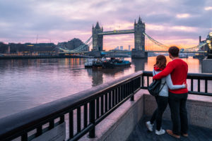 A couple stands arm in arm in London at Tower Bridge for sunrise.