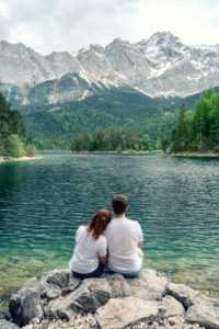 A couple in love sits at the Eibsee in Bavaria. In the background you can see the Zugspitze.