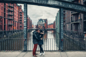 A couple is in Hamburg in front of the Speicherstadt and kisses.