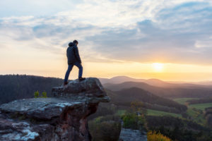 Hiker, young man, stands on vantage point, castle Drachenfels, Palatinate Forest, sunset.