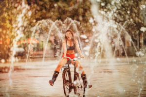 Young woman travels by bicycle through a fountain