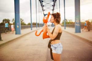 Young woman kissing an inflatable monkey